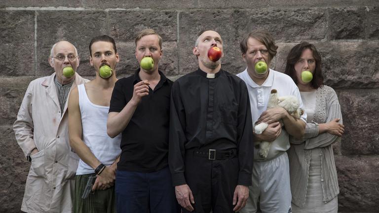 Sechs Personen nebeneinander stehend, die jeweils einen Apfel im Mund haben.