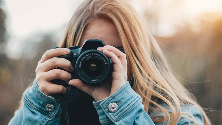 Fotografin mit Spiegelreflex-Kamera in der Hand