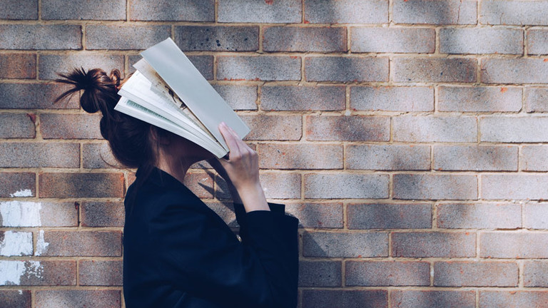 Frau mit einem Buch vor dem Gesicht.
