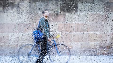Radfahrer mit Fahrrad im Regen