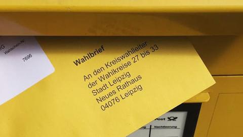 Detailfoto, Wahlbrief wird in einen gelben Briefkasten geworfen
