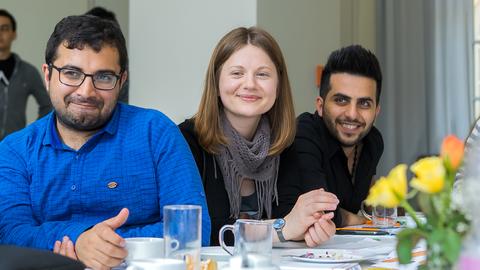 Drei lächelnde internationale Studierende bei einer Veranstaltung, die jemandem zuhören.