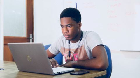 Ein Student sitzt aufmerksam vor seinem Laptop.