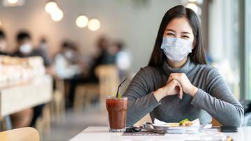 Frau mit Maske sitzt in der Mensa und lächelt