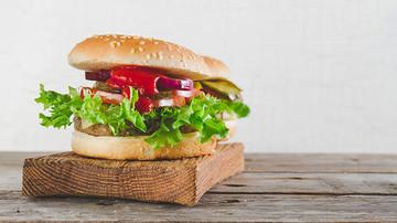 Leckerer Burger, angerichtet auf einem Holzbrett