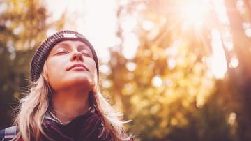 Junge Frau mit Mütze in der Natur mit geschlossenen Augen