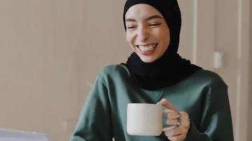 Studentin mit Kopftuch und einem breiten Lachen hat eine Tasse Kaffee in der Hand und schaut in ihren Laptop