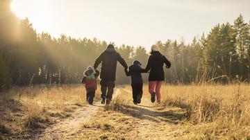 Eine Familie läuft einen Waldweg entlang.
