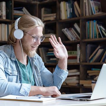 Student mit Headset telefoniert über Laptop und winkt